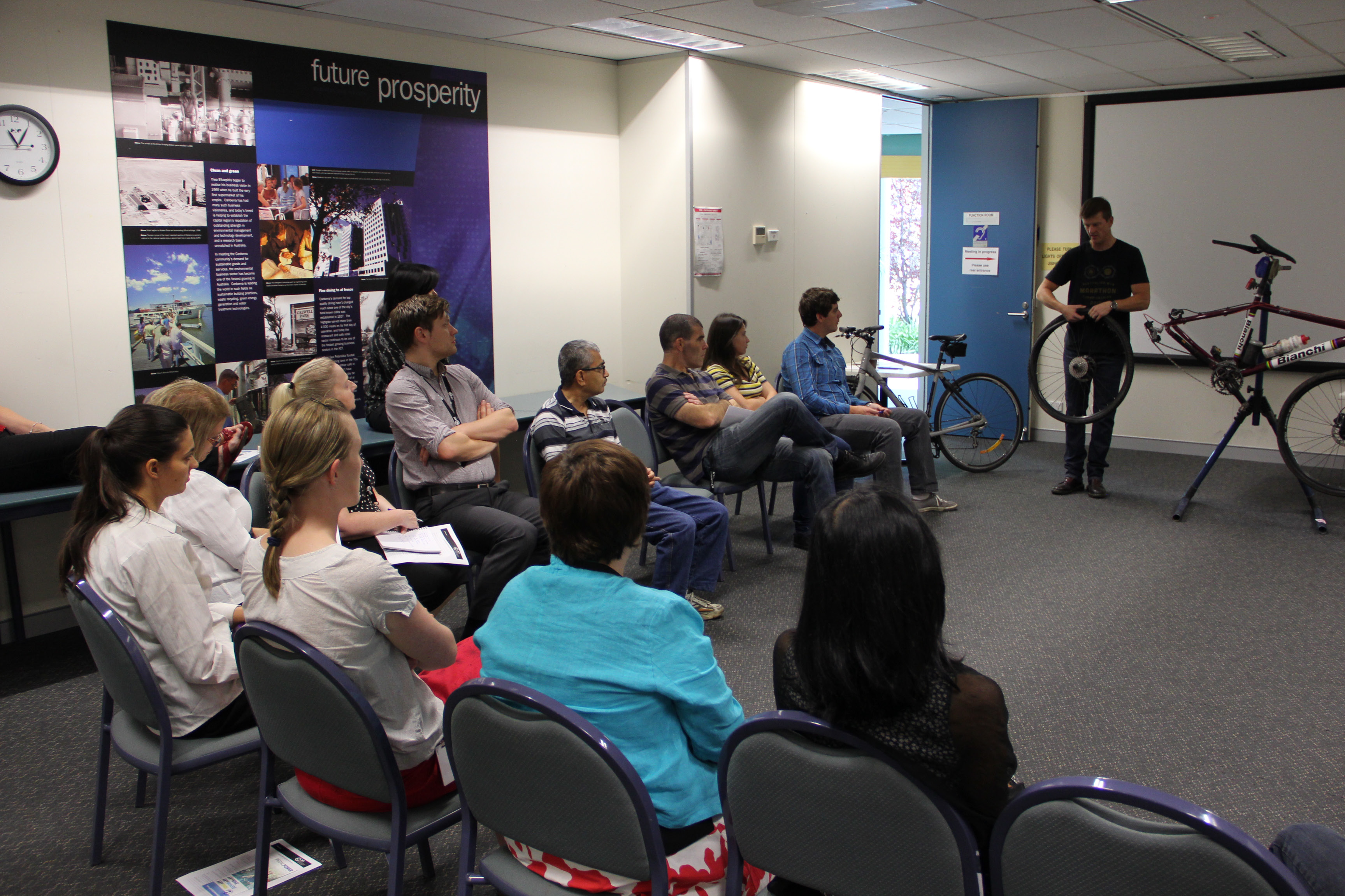Members of staff watching a trainer with a dismantled bicycle as a prop explaining bike maintenance and road safety