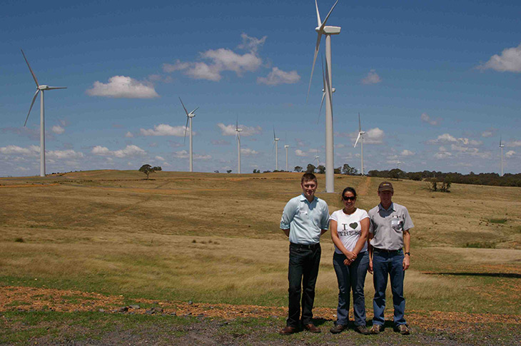 Three of the Directorate's staff standing in front of some wind turbines